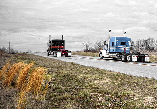Kenworth W900Ls with 3-color paint driving on the back road